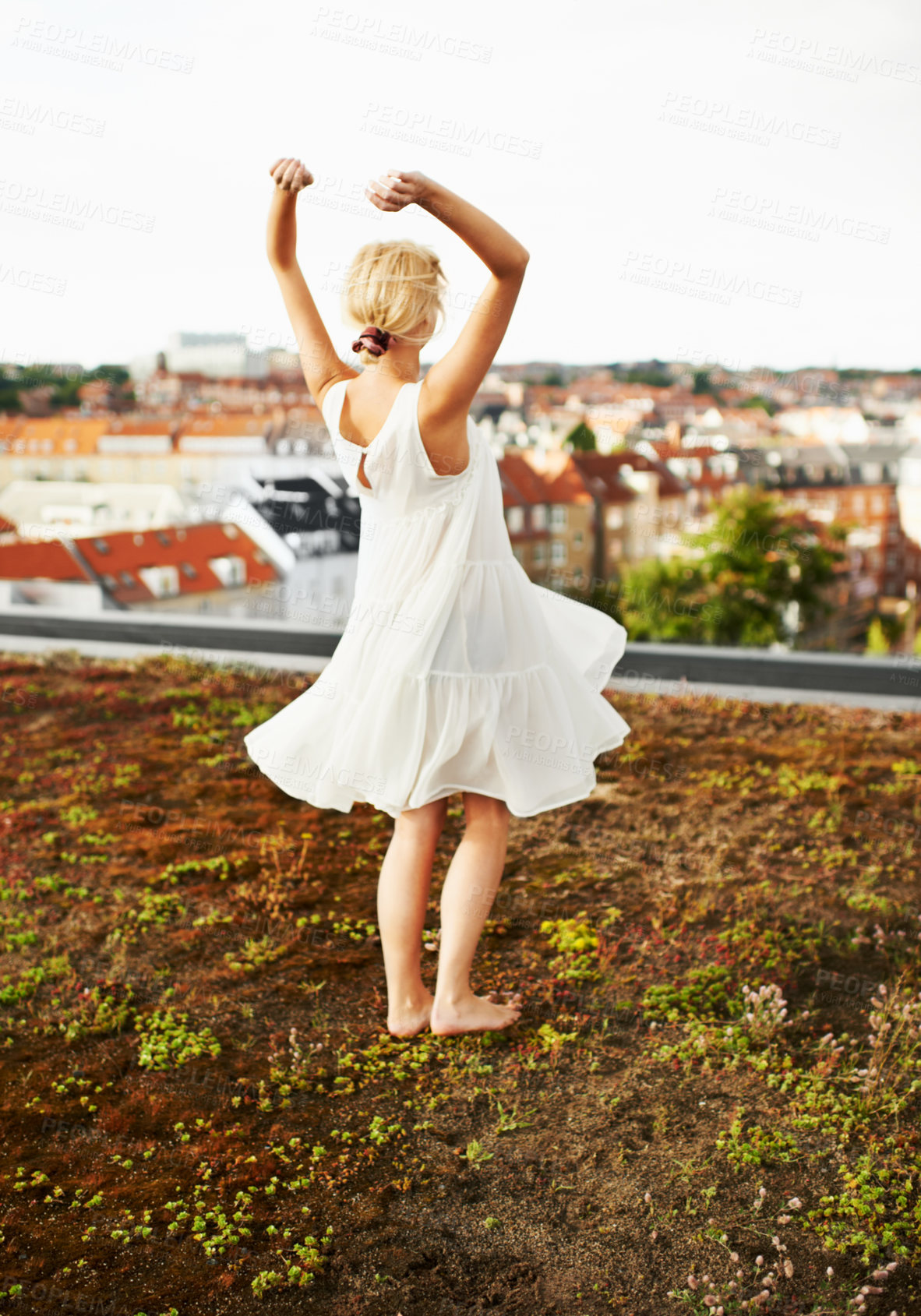 Buy stock photo A beautiful young woman dancing outside while looking at a city in the background