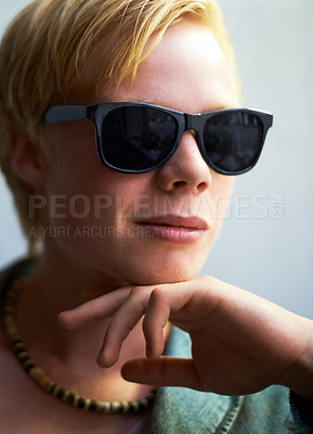 Buy stock photo Attractive young guy wearing hipster shades with his hand on his chin