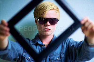 Buy stock photo Trendy young guy holding up a frame that frames his face