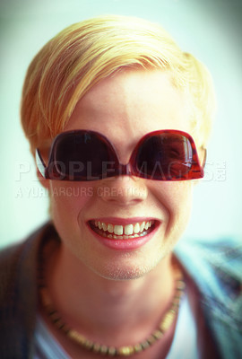 Buy stock photo Smiling young blonde guy with his hipster shades on upside-down