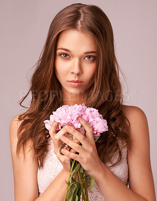 Buy stock photo Beautiful young woman holding a bunch of pink flowers against a pink background