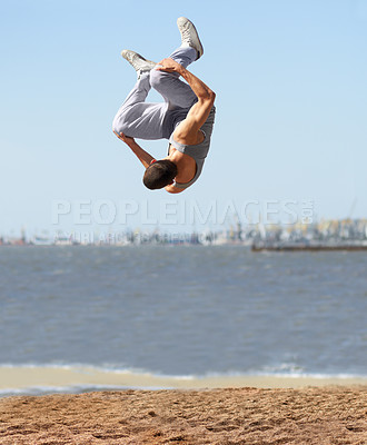 Buy stock photo An athletic young man doing a somersault at the beach