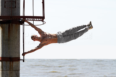 Buy stock photo A muscular young man practicing parkour at the beach