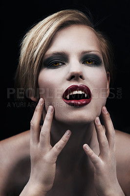 Buy stock photo A seductive female vampire with blood red lips against a dark background