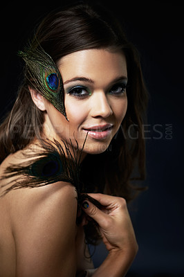 Buy stock photo A gorgeous young woman with dramatic eye makeup holding a peacock feather