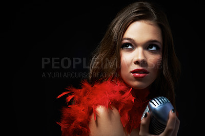 Buy stock photo Shot of an attractive young singer holding an old-fashioned microphone