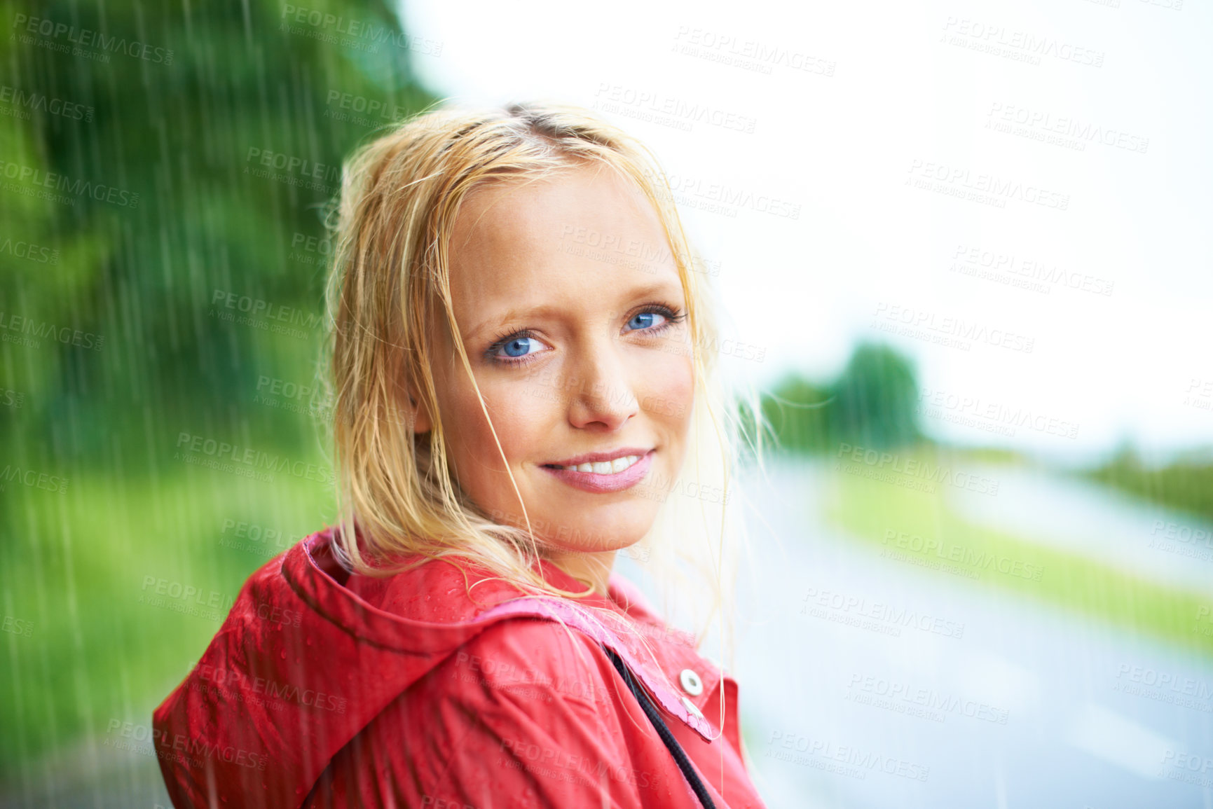 Buy stock photo Gorgeous young blonde woman wearing a red raincoat in the rain outdoors on a country road