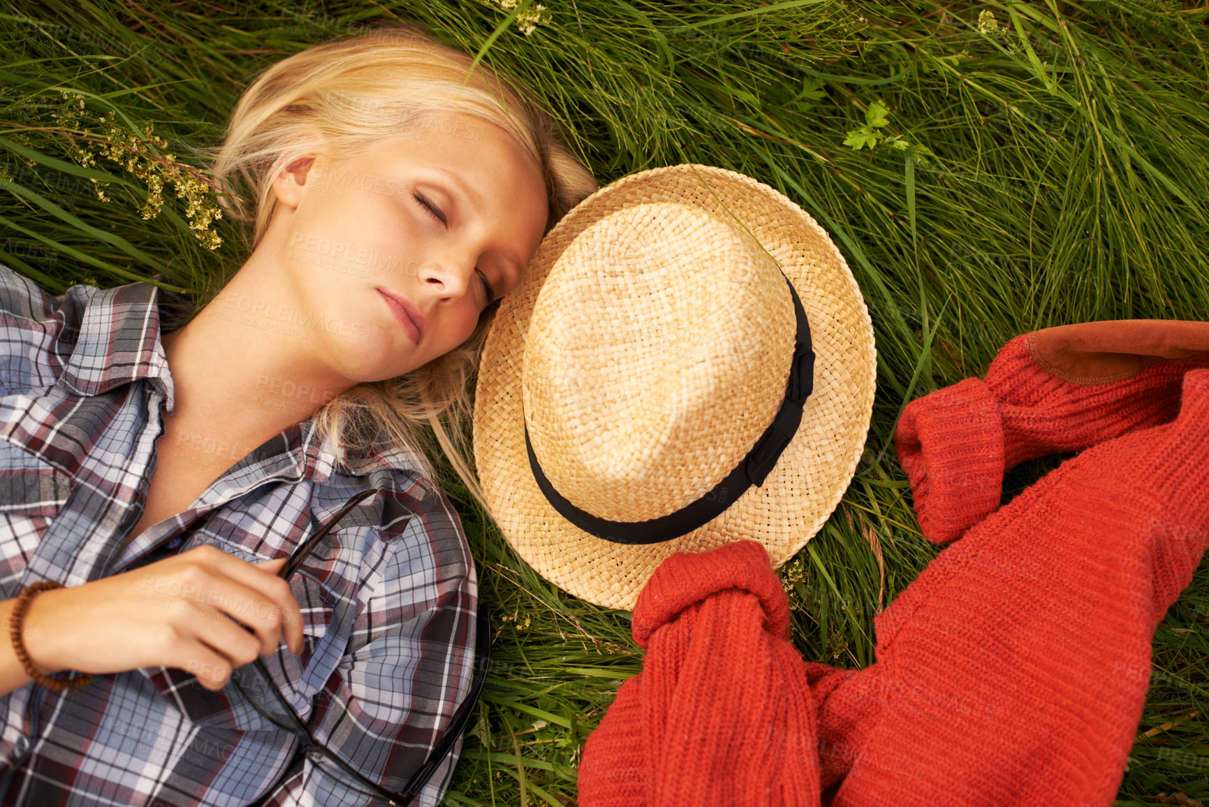 Buy stock photo Beautiful young blonde woman asleep in a field with her hat and coat alongside