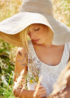Buy stock photo Gorgeous young beauty picking wildflowers in a field while wearing a straw hat
