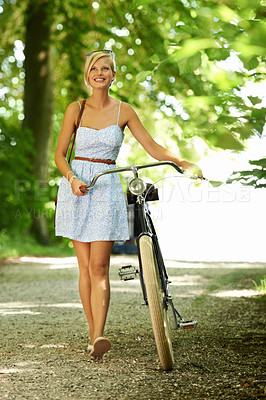Buy stock photo Pretty young woman walking through a tree-lined country path while pushing her bicycle