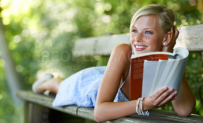 Buy stock photo Pretty young woman lying on a bench and reading her book outdoors