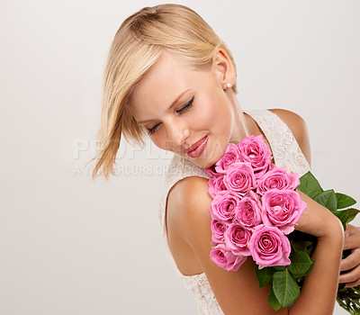 Buy stock photo An attractive young woman holding a bouquet of flowers with her eyes closed