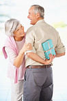 Senior happy husband hiding a gift in front of his curious wife