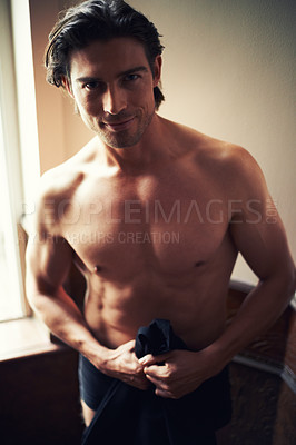 Buy stock photo Portrait of a handsome young man standing shirtless near a window