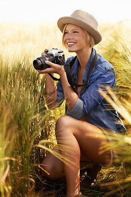 Buy stock photo An attractive young woman holding a camera while crouched in a field