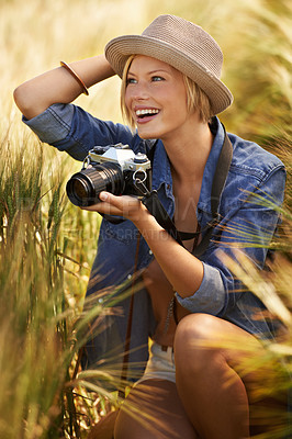 Buy stock photo An attractive young woman holding a camera and looking surprised in an open field