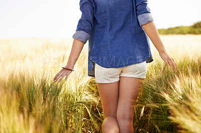 Buy stock photo Cropped image of a young woman walking in an open field