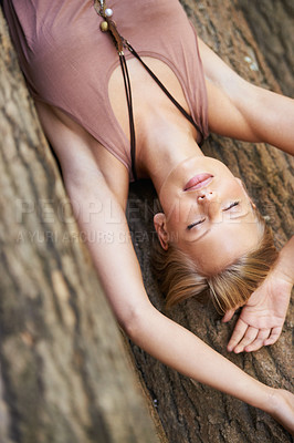 Buy stock photo A young woman lying down with her eyes closed on the forest floor