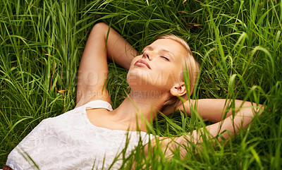 Buy stock photo An attractive young woman sleeping in an open green field