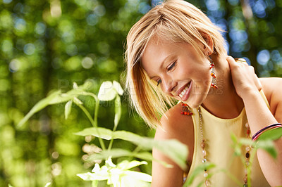 Buy stock photo An attractive young woman looking at the plants in nature