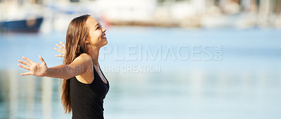 Buy stock photo A gorgeous young woman standing with arms outstretched at the harbour