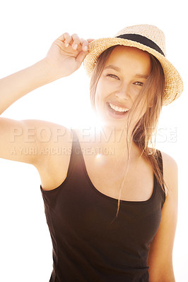 Buy stock photo A playful young woman holding her hat in bright sunlight