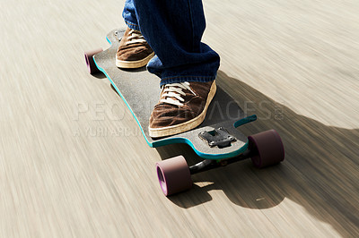 Buy stock photo Cropped shot of a man riding a skateboard at high speed