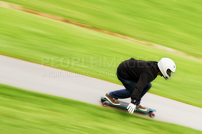 Buy stock photo Shot of a man skateboarding down a lane at high speed on his board