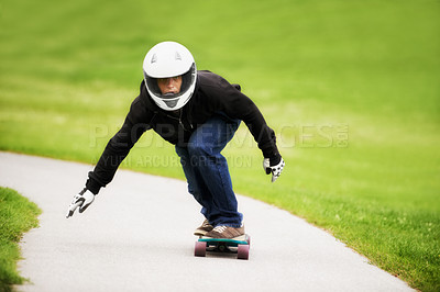 Buy stock photo Shot of a skateboarder making his way down a lane on his board