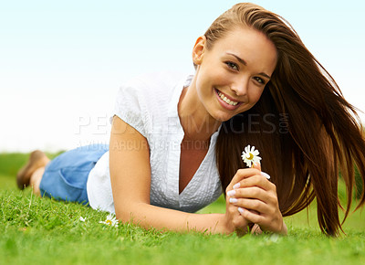 Buy stock photo Cute young woman smiling and holding a flower while lying on the grass