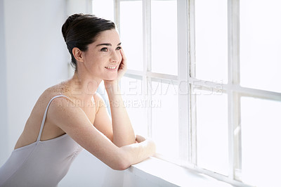 Buy stock photo Smiling young ballerina looking out of a window