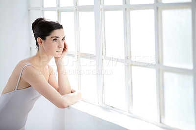 Buy stock photo Thoughtful young ballerina looking out of a window