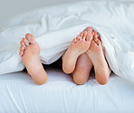 Couple in bed , focus on their feet