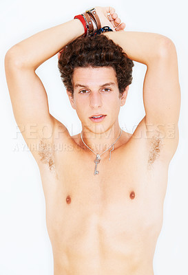 Buy stock photo Studio portrait of a bare-chested young man with his hands resting on the top of his head