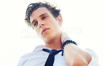 Buy stock photo Low angle portrait of a handsome and stylish young man with his hand behind his head