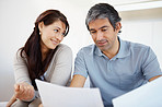 Happy mature couple discussing their finances at home