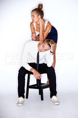 Buy stock photo Portrait of a young man sitting on a chair with a girl leaning on his back