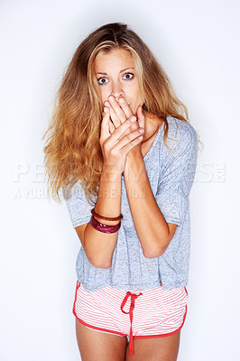 Buy stock photo Portrait of a pretty young woman covering her mouth in shock on a white background