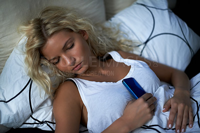 Buy stock photo Shot of a young woman sleeping while holding on to her cellphone