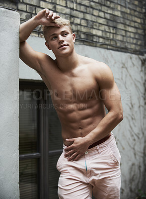 Buy stock photo Shot of a muscular young man leaning against a wall and looking away thoughtfully