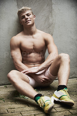 Buy stock photo Shot of a muscular young man leaning against a wall and looking at you confidently