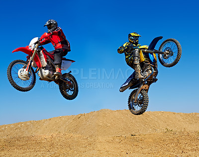Buy stock photo Action shot of two dirt bikers jumping in different directions