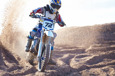 Buy stock photo A motocross rider riding towards the camera with dirt flying up behind him