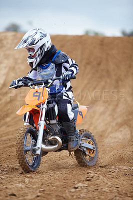 Buy stock photo A young motocross rider coming down a hill on a dirt track