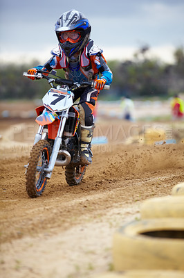 Buy stock photo A young motocross rider coming round a bend on a track