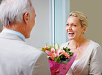 Man offering bouquet to surprised wife