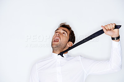 Buy stock photo Handsome young guy yelling while being strangling himself with his neck tie