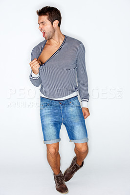 Buy stock photo Handsome young man pulling at the neck of his sweater and yelling while against a white background