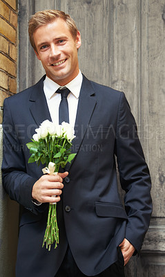 Buy stock photo Portrait of a handsome man smiling and holding a bunch of white roses