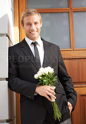 Buy stock photo Portrait of a handsome man leaning against a wall holding a bunch of white roses and smiling